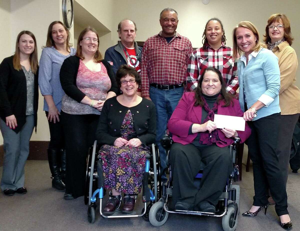 The Independent Living Center of the Hudson Valley,(ILCHV) accepts a donation from First Niagara Financial Group. ILCHV is a non-profit organization supporting people with disabilities becoming independent in their own communities. Kelli Arnold from First Niagara Financial Group is pictured handing the check to Denise FIgueroa, ILCHV Executive Director. Also pictured are (first row) Barbara Devore, Director of Development, back row: Kim Arnold, Transition Specialist; Anna Gowdy, Coordinator of Community Health Advocacy Programs, Lyndsi Wickert, Youth Specialist; Sean Turley, Board President; Cliff Perez, Systems Advocate; Melody Singletary, Facilitated Enroller; and Pat Pfeifer, Coordinator of the Open Door program. ILCHV was one of five non-profits awarded funding from the proceeds of the sale of the historic Rice Building.