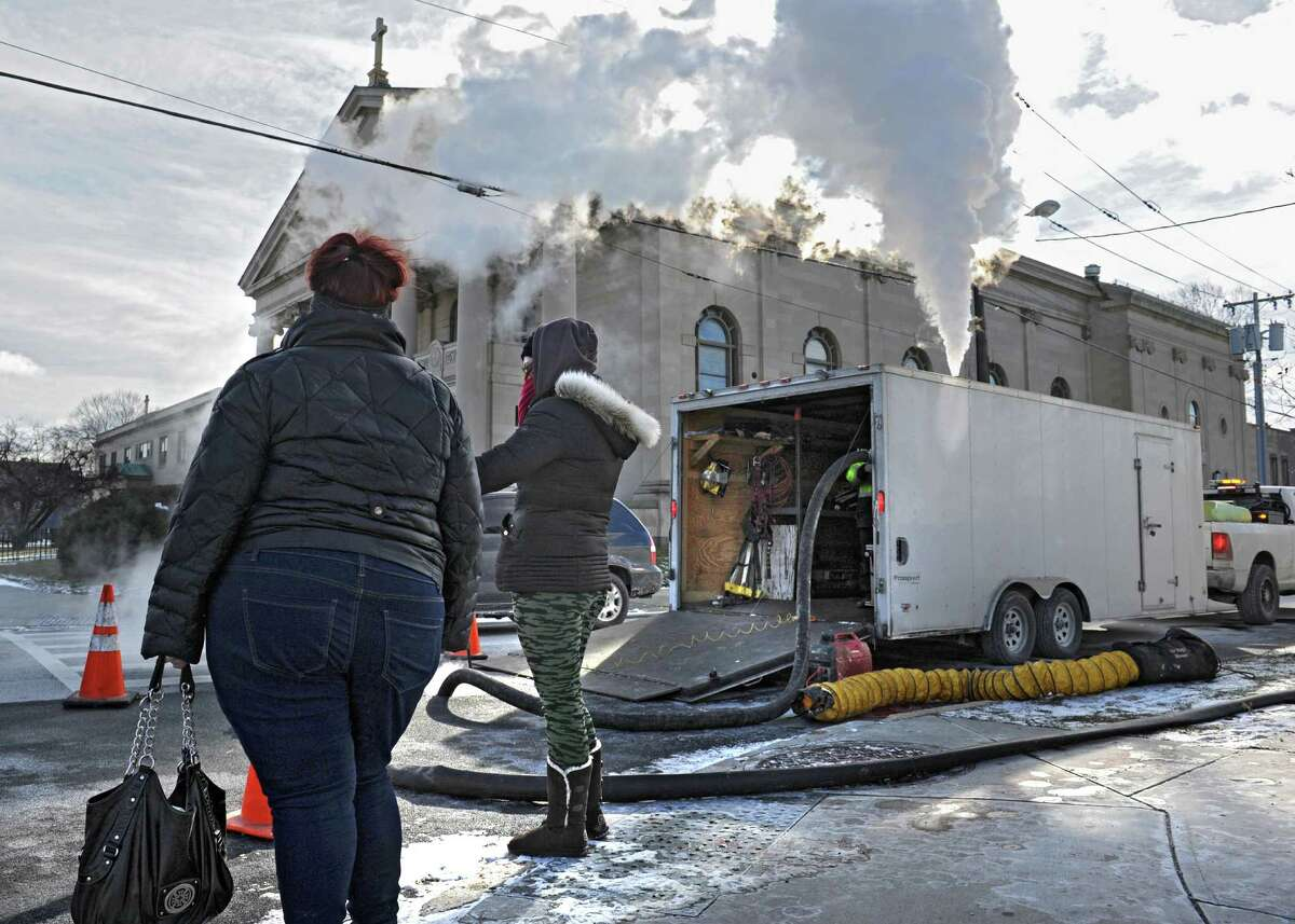 People walk by a crew from Kenyon Pipeline Inspection who are re-lining a sewer pipe at the corner of Madison Ave. and Partridge St. on Tuesday, Jan. 19, 2016 in Albany, N.Y. The steam looked dense in the frigid weather.(Lori Van Buren / Times Union)