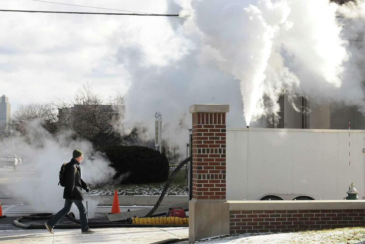 A person walks by a crew from Kenyon Pipeline Inspection who are re-lining a sewer pipe at the corner of Madison Ave. and Partridge St. on Tuesday, Jan. 19, 2016 in Albany, N.Y. The steam looked dense in the frigid weather.(Lori Van Buren / Times Union)