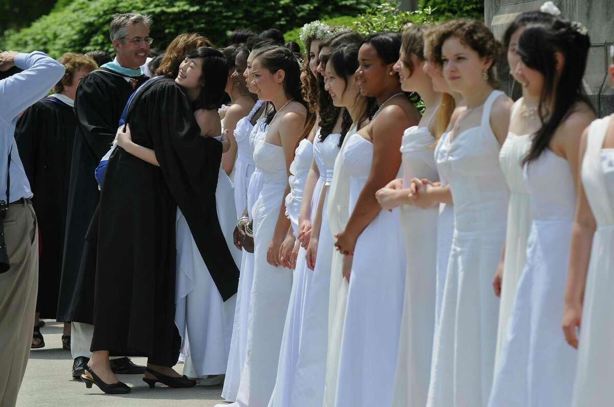 Trudy E. Hall, head of school, greets graduates on the