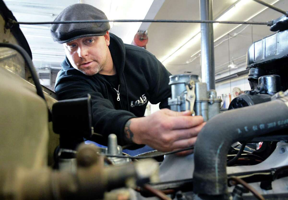 Jeremy Baye adjusts a carburetor on a 1936 Ford Woody Wagon at his 1945 Speed and Custom Shop Tuesday Jan. 19, 2016 in Troy, NY. (John Carl D'Annibale / Times Union)