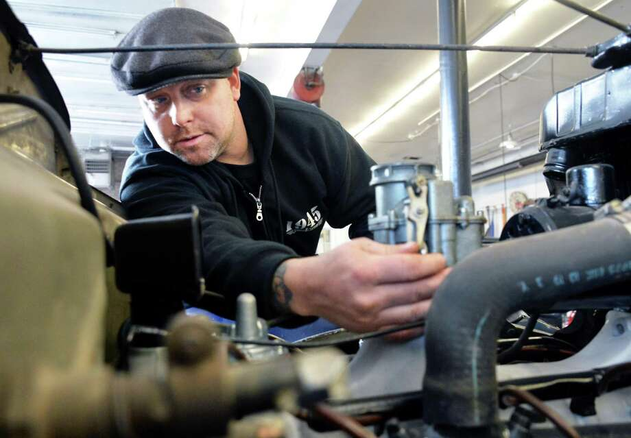 Jeremy Baye adjusts a carburetor on a 1936 Ford Woody Wagon at his 1945 Speed and Custom Shop Tuesday Jan. 19, 2016 in Troy, NY.  (John Carl D'Annibale / Times Union) Photo: John Carl D'Annibale / 20035054A