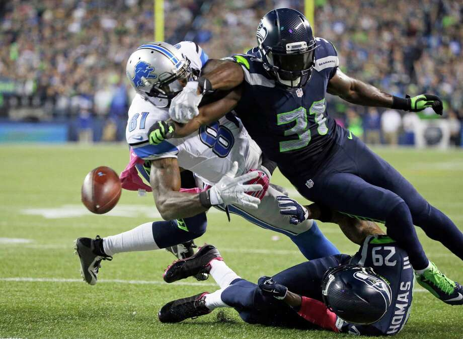 Seattle Seahawks strong safety Kam Chancellor (31) knocks the ball loose from Detroit Lions wide receiver Calvin Johnson (81) in the second half of an NFL football game, Monday, Oct. 5, 2015, in Seattle. The fumble went out of bounds in the end zone and was ruled a touchback. The Seahawks beat the Lions 13-10.  (AP Photo/Elaine Thompson) Photo: Elaine Thompson, Associated Press / AP
