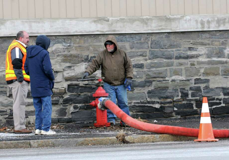 Officials and city workers stand next to a hydrant and hose that runs across the Cohoes-Waterford bridge to provide temporary water service to Waterford on Tuesday, Jan. 19, 2016 in Cohoes, N.Y.  A 33-inch water main that blew out in Troy on Sunday. (Lori Van Buren / Times Union) Photo: Lori Van Buren / 10035063A