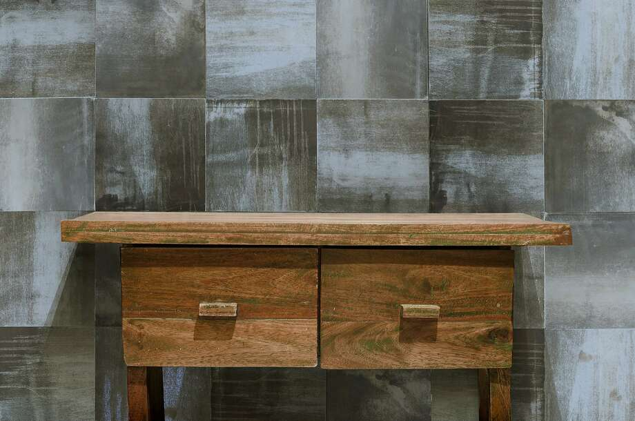 "Artist John Whitmarsh's ""Weathered Steel"" tiles behind a vintage wooden table. Photo: Cle Tile"