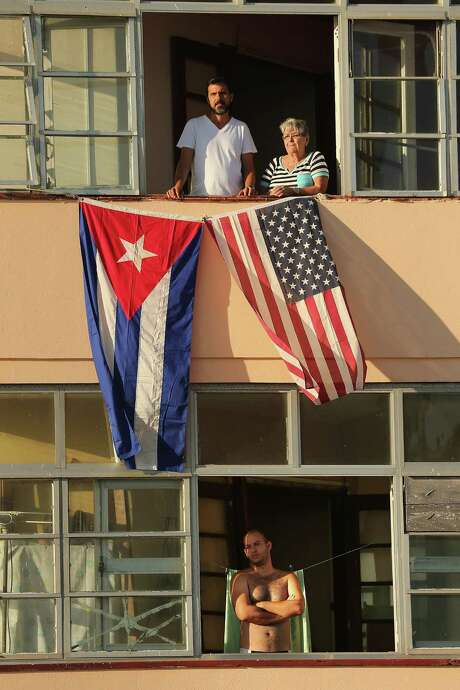 Cubans look out their window across the street from the newly reopened U.S. Embassy in hopes of watching the flag-raising ceremony Aug. 14, 2015 in Havana, Cuba. The first American secretary of state to visit Cuba since 1945, Secretary of State John Kerry visited the reopened embassy, a symbolic act after the the two former Cold War enemies reestablished diplomatic relations in July. (Photo by Chip Somodevilla/Getty Images) Photo: Chip Somodevilla, Staff / 2015 Getty Images
