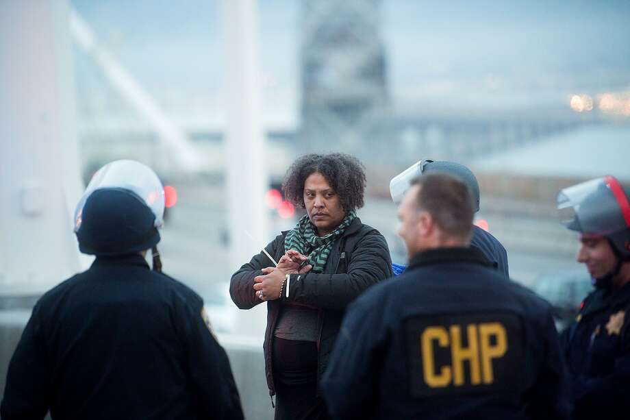 California Highway Patrol officers detain a woman on the Bay Bridge after a group of protesters blocked traffic for an hour on Martin Luther King Jr. Day. Photo: Noah Berger, Associated Press
