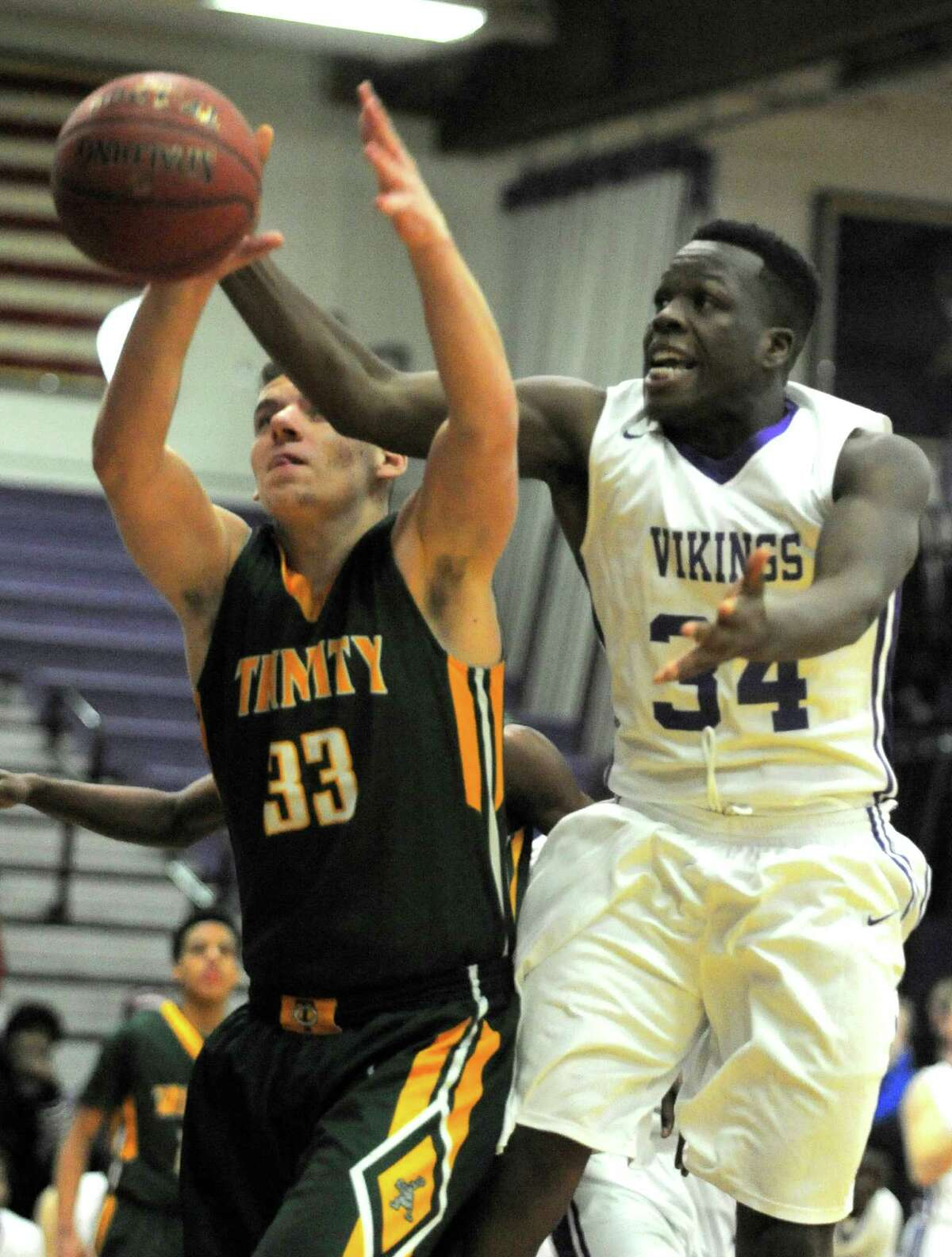 Trinity's Thomas Tamiolakis (33) and Westhill's Nate Jefferson (34) battle for a rebound in the second quarter of a FCIAC basketball game in Stamford, Conn. on Tuesday, Jan. 19, 2016.Westhill defeated Trinity Catholic 52-45.
