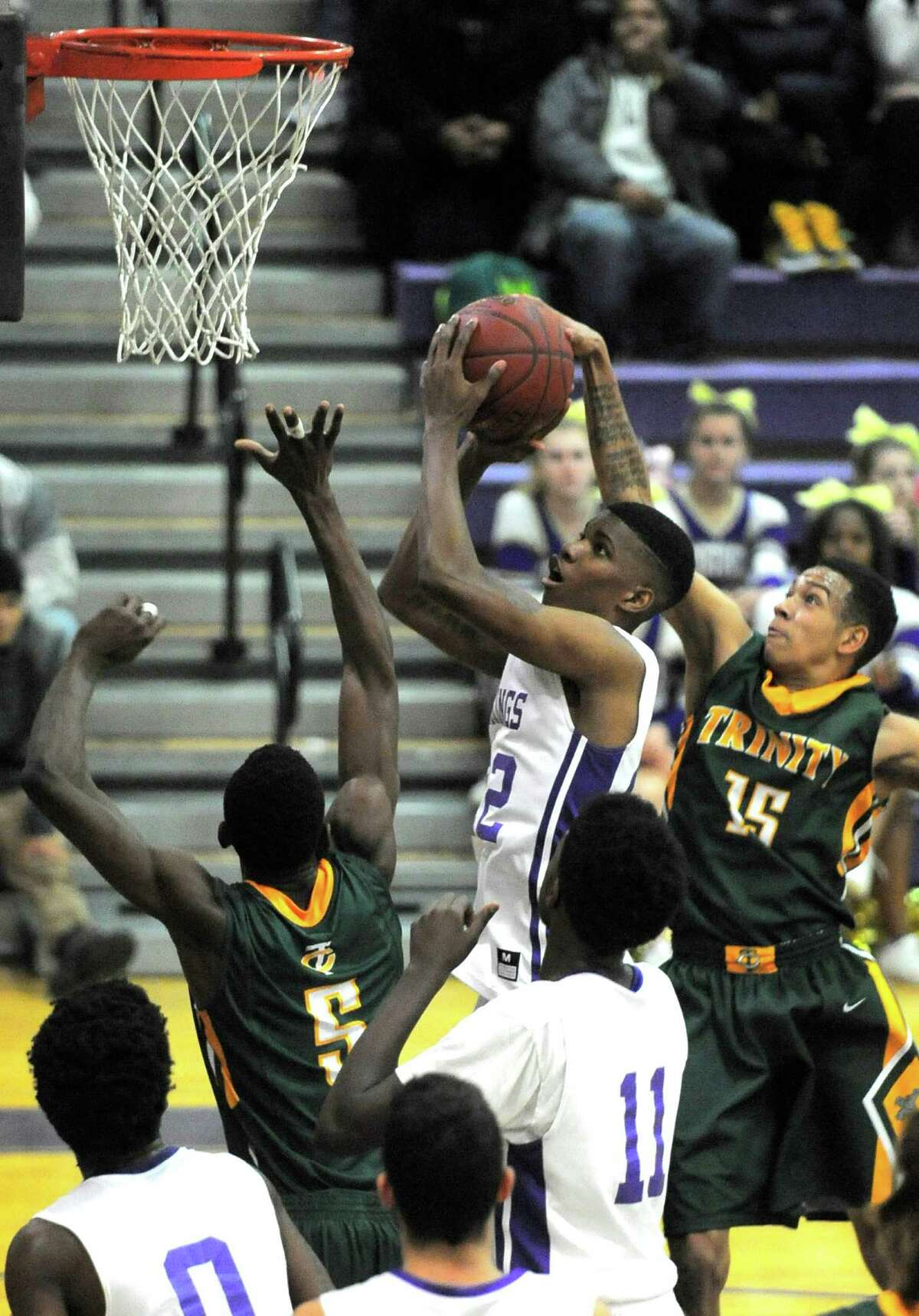 Westhill's Vashon Nattel (22) puts up a shot between Trinity's Dutreil Contavio (5) and Bryce Lucas (15) in the second quarter of a FCIAC basketball game in Stamford, Conn. on Tuesday, Jan. 19, 2016.Westhill defeated Trinity Catholic 52-45.