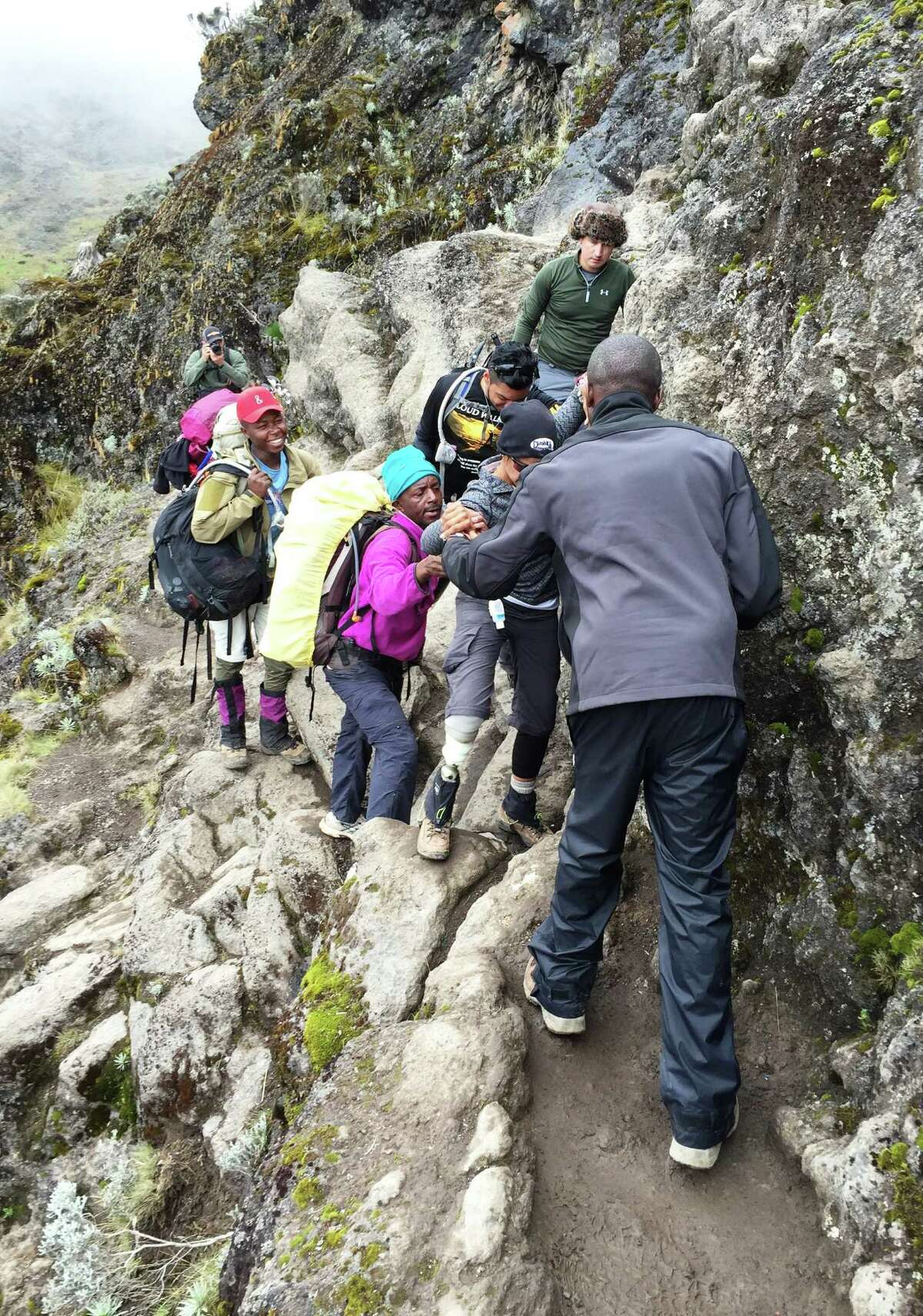 Porters and members of the Cloud Walkers assist one another as they tackle the narrow path of Barranco Wall, one of the most notable challenges of climbing Mt. Kilimanjaro.