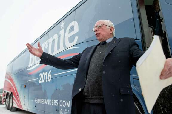 Democratic presidential candidate Sen. Bernie Sanders jokes with members of the media and pretends to slip as he steps off his bus before speaking Tuesday in Carroll, Iowa.