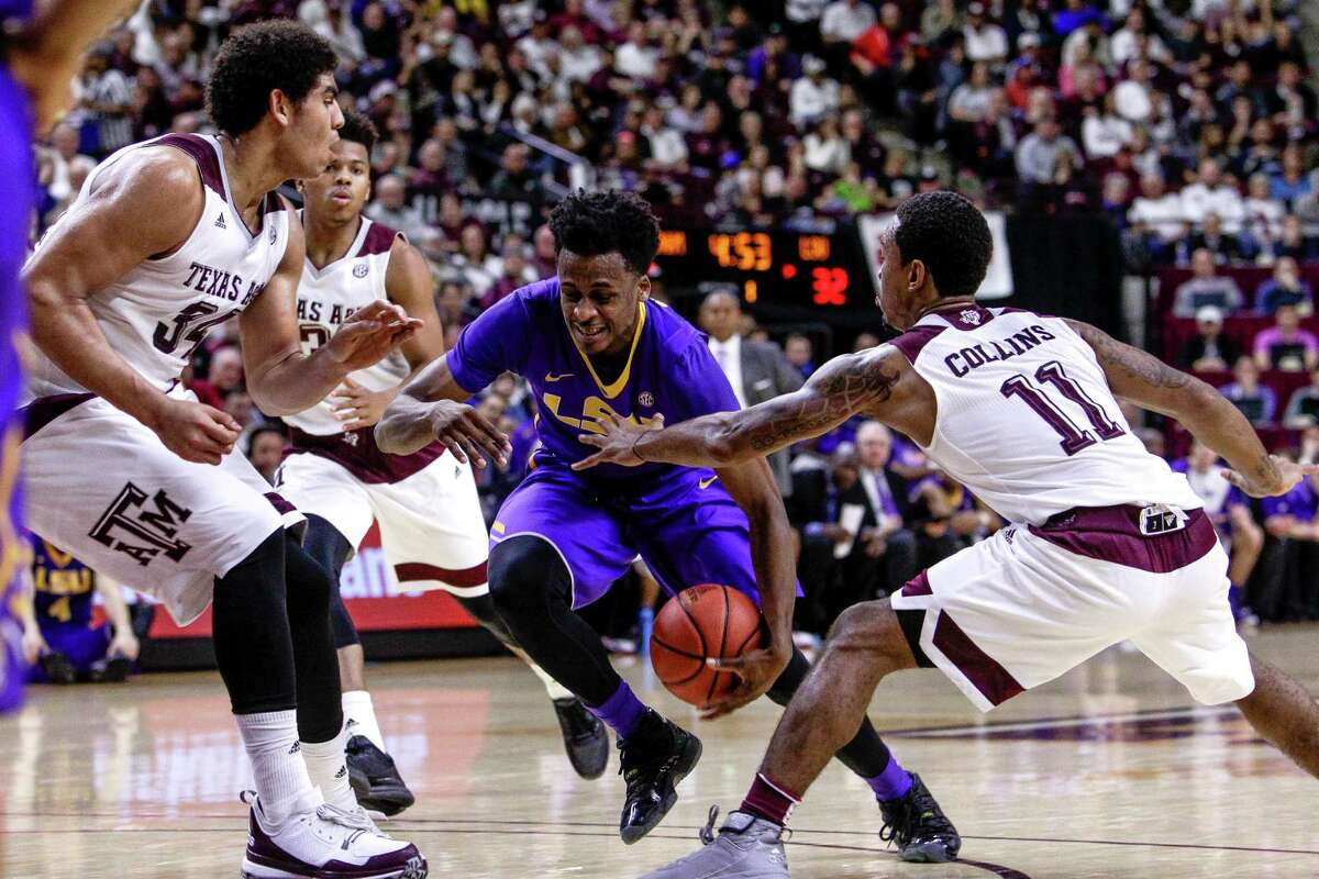 Texas A&M Aggies center Tyler Davis (34), left, and Texas A&M Aggies guard Anthony Collins (11), right, defend againt LSU Tigers guard Antonio Blakeney (2) as he heads toward the basket as Texas A&M takes on LSU Tuesday, Jan. 19, 2016, in College Station.
