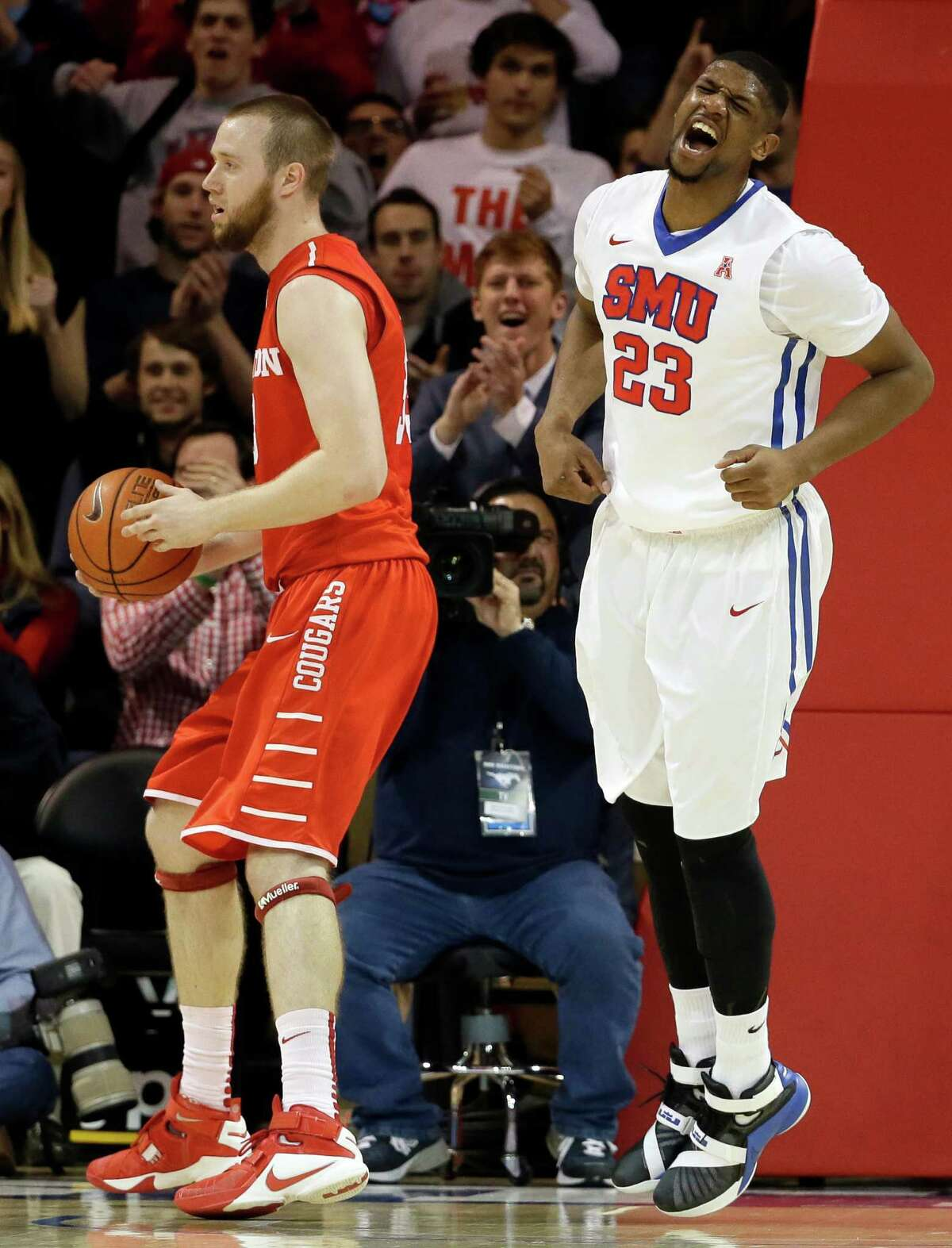 Houston center Kyle Meyer looks to the bench as SMU forward Jordan Tolbert (23) celebrates sinking a basket in the first half of an NCAA college basketball game, Tuesday, Jan. 19, 2016, in Dallas. (AP Photo/Tony Gutierrez)