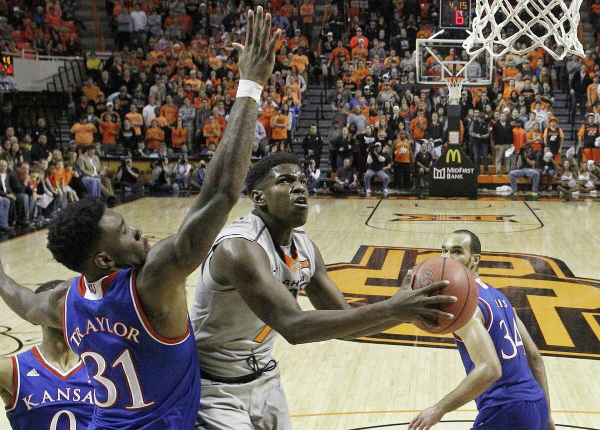 Oklahoma State guard Jawun Evans (1) goes up for a shot between Kansas forward Jamari Traylor (31) and forward Perry Ellis (34) in the second half of an NCAA college basketball game in Stillwater, Okla., Tuesday, Jan. 19, 2016. Oklahoma State won 86-67. (AP Photo/Sue Ogrocki) ORG XMIT: OKSO106