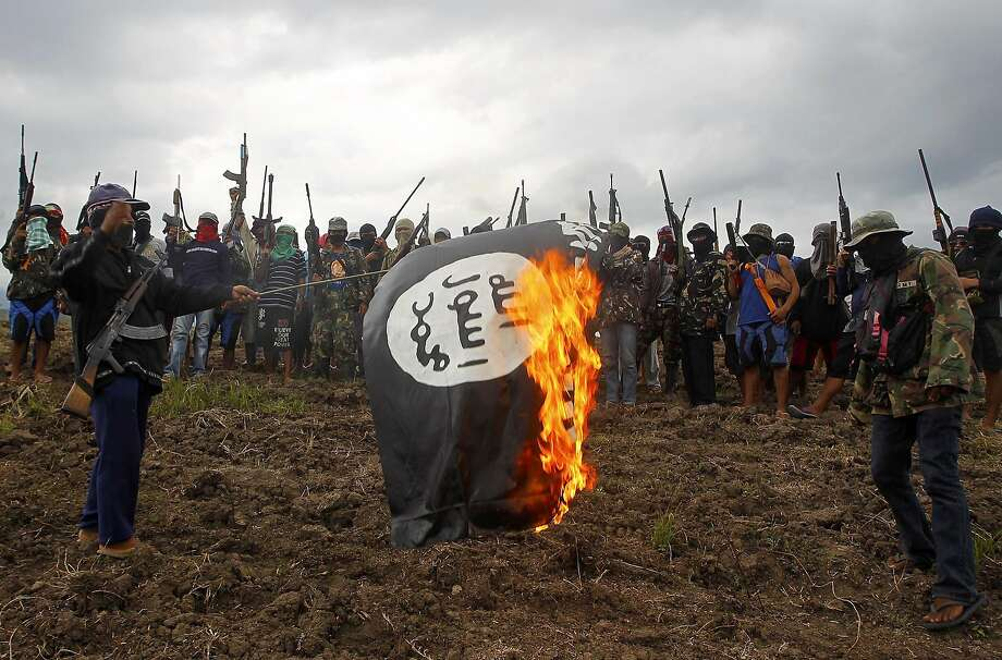 Members of an armed Philippine Christian group calling themselves Red Gods defenders (Pulahan) burn a blag flag at an unspecified area somewhere in the Central Mindanao mountains on January 19, 2016. The group burned a black flag similar to one used by Islamic State jihadists, vowing to fight any attempt spread its roots in the Asian country. Photo: Mark Navales, AFP / Getty Images