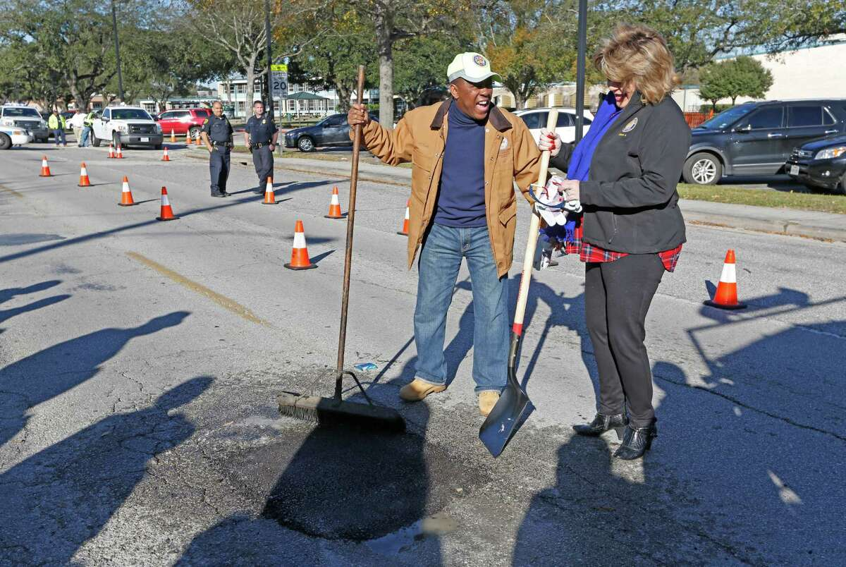 City Council District A Brenda Stardig and Mayor Sylvester Turner laugh after filling a pothole at 9733 Neuens Road on Jan. 19.