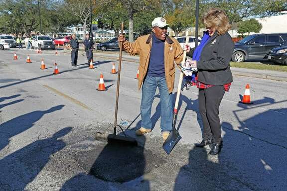 City Council District A Brenda Stardig and Mayor Sylvester Turner laugh after filling a pothole at 9733 Neuens Road, Tuesday, Jan. 19, 2016, in Houston to mark the formal start of his pothole repair program.  The program  also included the debut of a new website for tracking pothole repair progress, and a new customer service plan that includes electronic or phone outreach to each individual who reports a pothole.