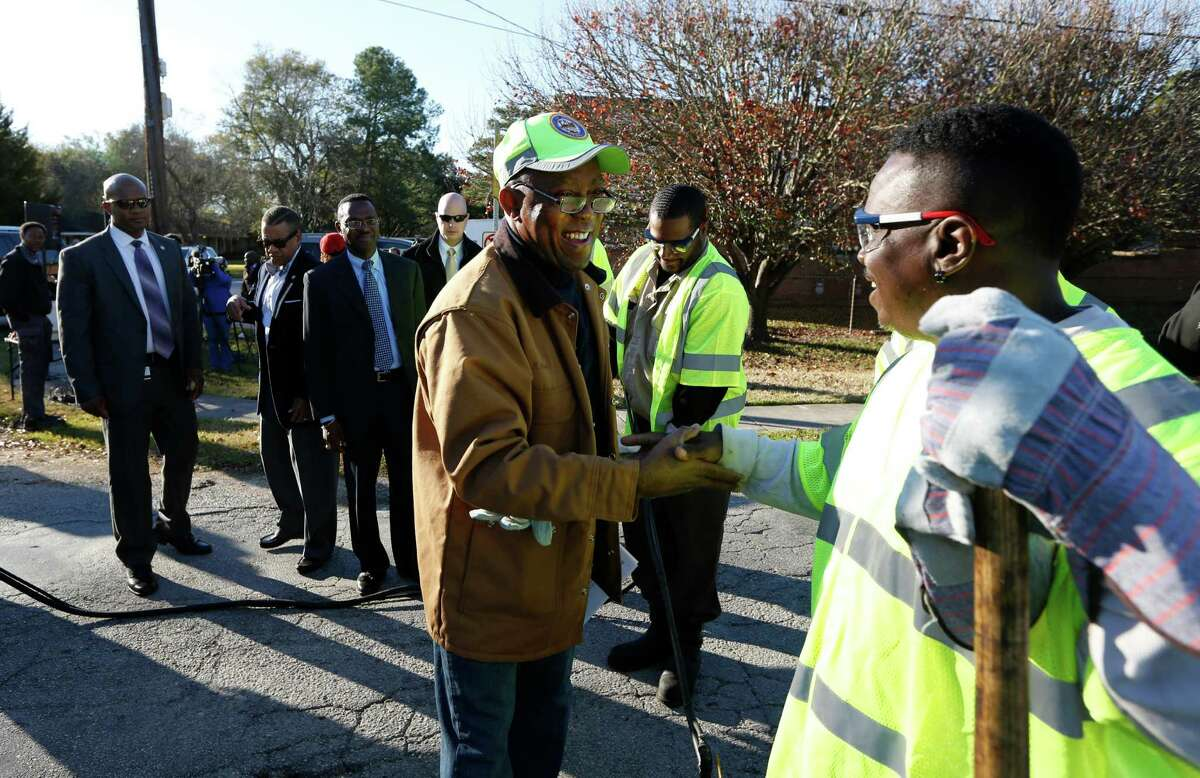 Mayor Sylvester Turner shakes hands with Kevin Moore before filling a pothole at 9733 Neuens Road, Tuesday, Jan. 19, 2016, in Houston. The program also included the debut of a new website for tracking pothole repair progress, and a new customer service plan that includes electronic or phone outreach to each individual who reports a pothole.