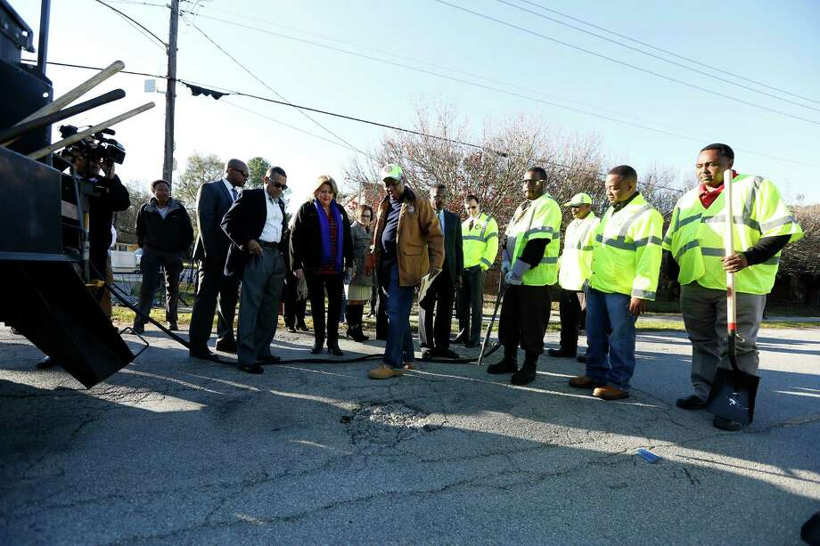 Before his press conference, Mayor SylvesterTurner looks at the pothole he would repair at 9733 Neuens Road, Tuesday, Jan. 19, 2016, in Houston. The program  also included the debut of a new website for tracking pothole repair progress, and a new customer service plan that includes electronic or phone outreach to each individual who reports a pothole. Photo: Steve Gonzales, Houston Chronicle / © 2016 Houston Chronicle