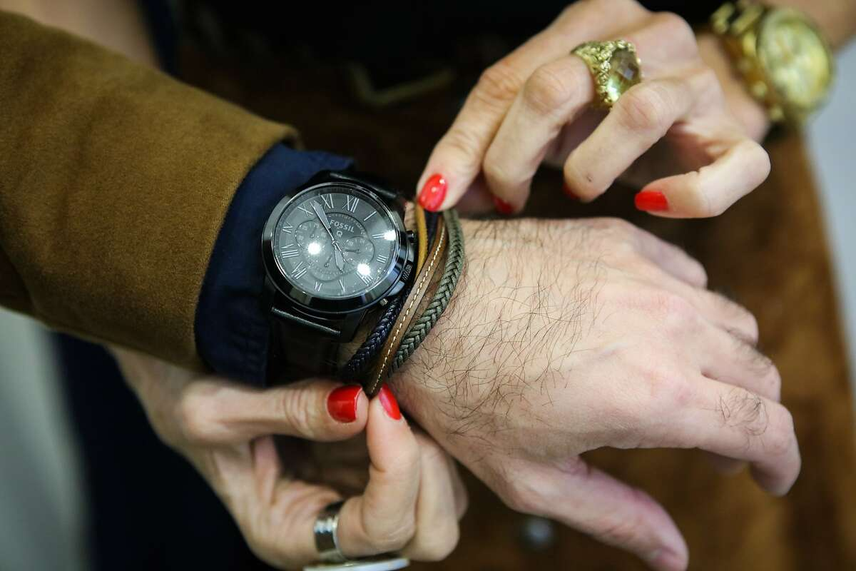Fashion consultant Victoria Hitchcock (right) puts leather braided bracelets on Damon Schechter (left) wrist, during a private styling session, at store Denim & Soul, in San Francisco, California on Friday, January 15, 2016.