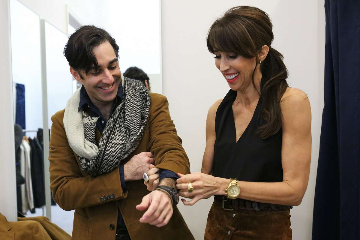 Damon Schechter (left), rolls up his sleeves, as fashion advisor Victoria Hitchcock (right), accessorizes him with a watch and bracelet, during a personal styling session, at boutique Denim & Soul, in San Francisco, California on Friday, January 15, 2016.