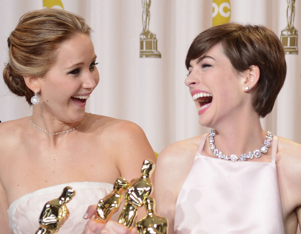 Actresses Jennifer Lawrence and Anne Hathaway pose in the press room during the Oscars held at Loews Hollywood Hotel on February 24, 2013 in Hollywood, California.