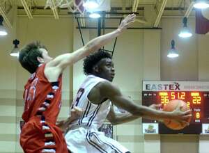 Silsbee's Travious Grubbs goes for the lay-up against the efforts of Hardin-Jefferson's Michael Saladin during their District 24-4A match-up Tuesday at Silsbee High School. Each team entered the court undefeated.  Photo taken Tuesday, January 19, 2016  Kim Brent/The Enterprise