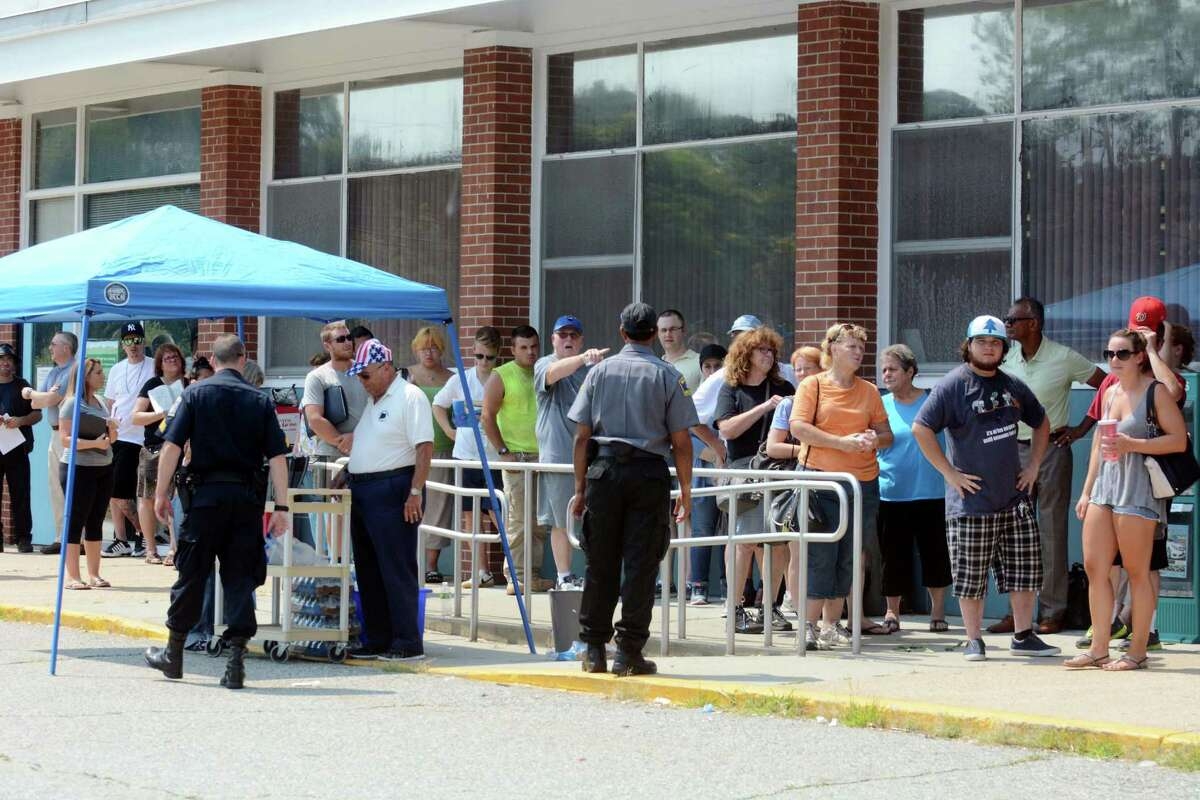 People wait on line outside the Norwich Motor Vehicle Department, Tuesday, Aug. 18, 2015 in Norwich, Conn. Connecticut's Department of Motor Vehicles has completed a major computer upgrade a few days early and says online services are available again. Branch offices have been closed for a week for the upgrade, and Commissioner Andres Ayala Jr. warns there will be long lines on Tuesday when offices reopen for registration-related services. (John Shishmanian/The Norwich Bulletin via AP) MANDATORY CREDIT