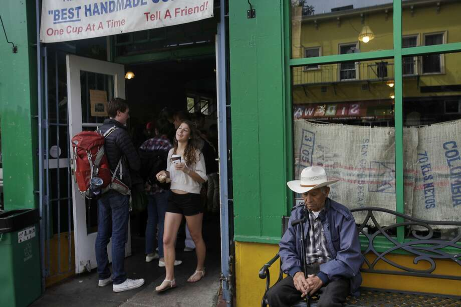 Longtime local resident Jose Luiz, 86, right, sits on a bench as people enter and exit the original Philz Coffee Aug. 8, 2014 in San Francisco, Calif. In 2003, Phil started the coffee shop in a grocery store he already owned on the corner of 24th and Folsom. Since then, Phil has opened 15 more shops in and around the Bay Area. Photo: Leah Millis, The Chronicle