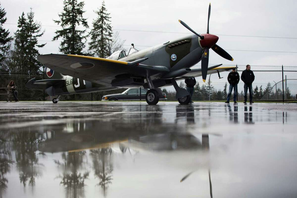 Mechanics Billy Kelly and Martin Overall wait for the test flight of the WWII Vickers Supermarine Spitfire they rebuilt earlier in the week at the Historic Flight Foundation in Mukilteo. The test flight was canceled due to weather.