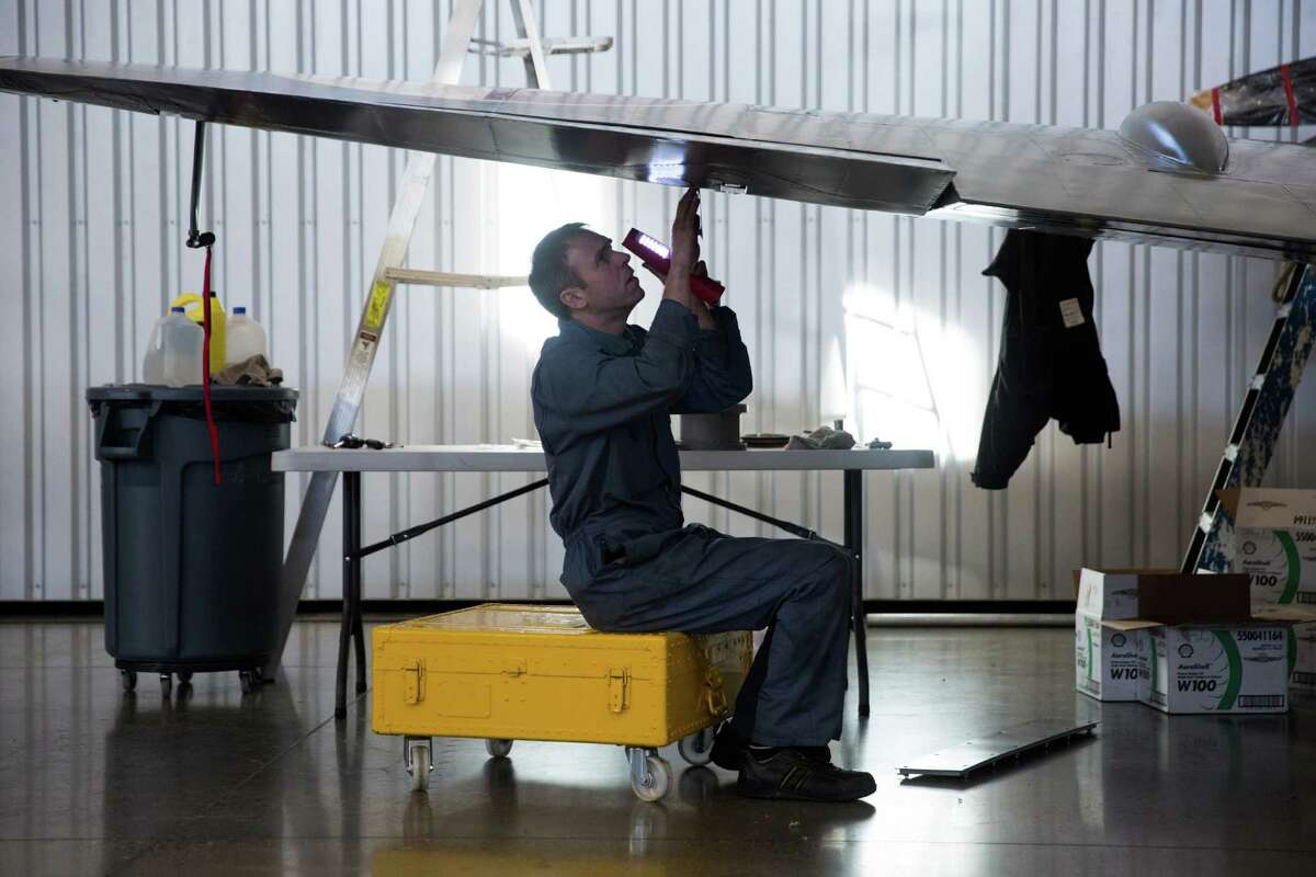 Martin Overall, an English airplane mechanic, works under the left wing of a WWII Vickers Supermarine Spitfire during its reassembly at the Historic Flight Foundation.