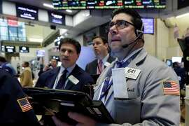 Michael Capolino, right, works with fellow traders on the floor of the New York Stock Exchange on Jan. 20. Energy stocks are leading another sell-off on Wall Street as the price of oil continues to plunge.