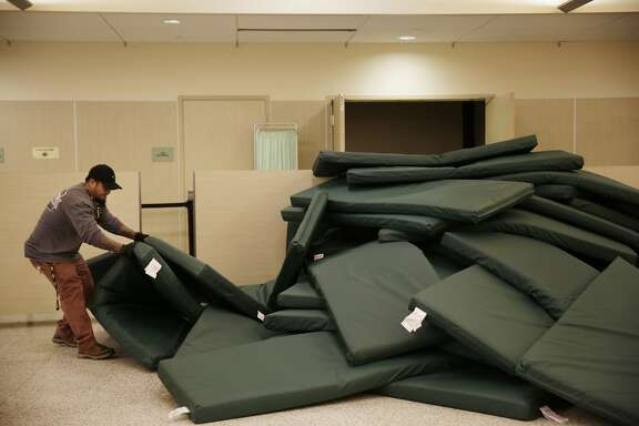 Rath Nou, shelter staff, picks up mats as he begins to arrange the beds in the evening for clients at the St. Anthony's emergency winter shelter on Tuesday, January 19, 2016 in San Francisco, Calif.
