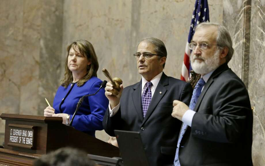 """Washington Lt. Gov. Brad Owen, center, counts votes on the Senate floor as Senate legal counsel look on. O)wen is retiring after 20 years as Washington's """"lite governor."""" (AP Photo/Ted S. Warren)"""