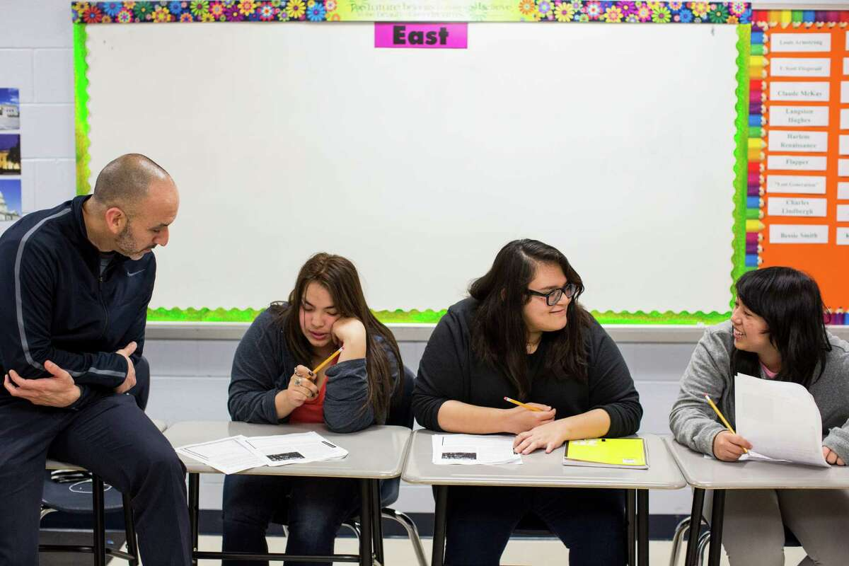 Johnny Macias (from left), helps Jazmin Dillard as Ashliegh Hernandez and Rose Martinez talk about their assignment in Cari Barta's U.S. history class at Tejeda Academy. The school currently doesn't meet the new 75,600 minutes rule, a district official said.