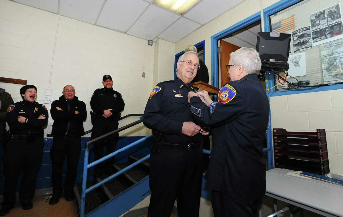 The longest serving member of the Stamford police department Sgt. Cliff Weed pins shield number one on the department's longest serving patrolman, Patrick Conetta during a shield reissuing ceremony inside the Stamford Police Department headquarters, at 850 Bedford Street on Jan. 20, 2016. The officers who previously held badges one through five recently retired, and the prestigious shields were then given to veteran members of the department.