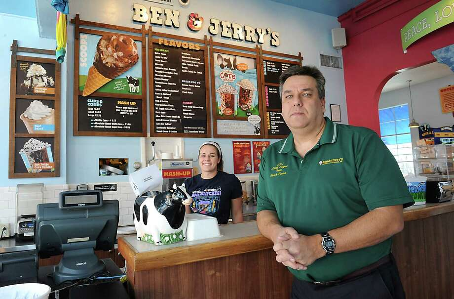 Owner Patrick Pipino, right, and employee Katie O'Connell stand inside the Ben and Jerry's on Phila Street Wednesday, Jan. 20, 2016 in Saratoga Springs, N.Y. Pipino is worried the minimum wage increase will put him out of business. (Lori Van Buren / Times Union) Photo: Lori Van Buren / 10035071A