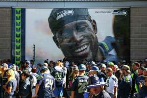 Fans line up outside CenturyLink Field under an image of Kam Chancellor before the Seattle Seahawks game against the Chicago Bears. It was Chancellor's first game back after holding out for the first part of the season. Photographed on Sunday, Sept. 27, 2015.