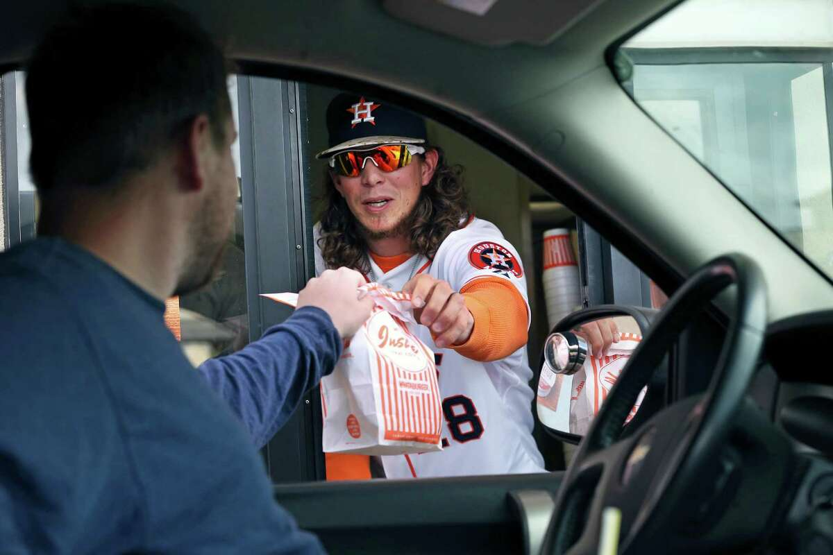 Colby Rasmus works the drive thru window as he and Astros teammate Brad Peacock stop at the Whataburger in the Rim Shopping Center during an Astros Winter Caravan stop on January 19, 2016.