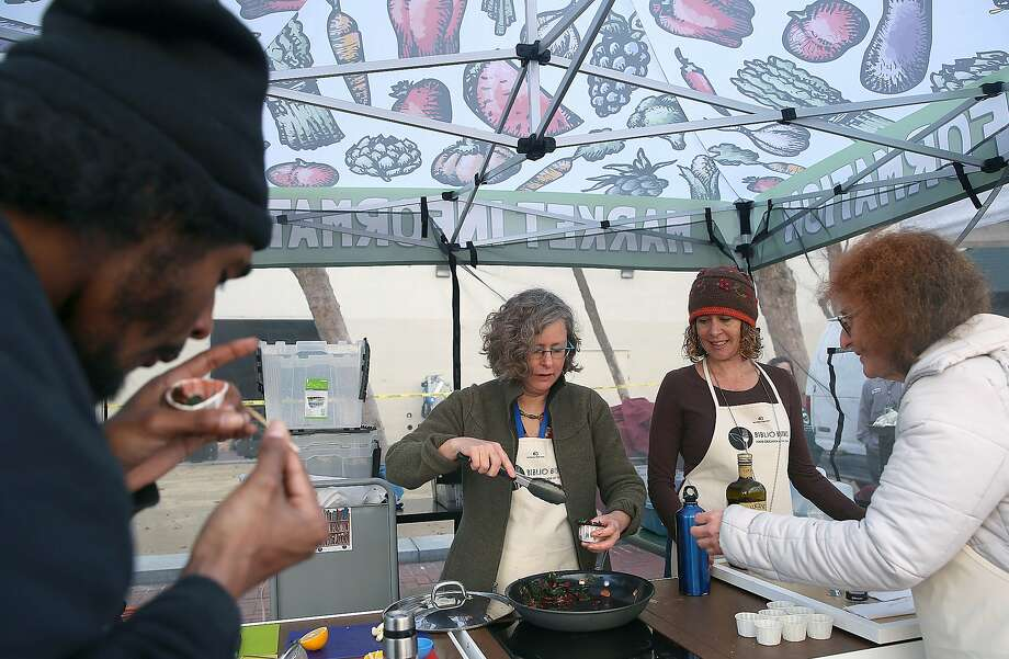 Left to right--Art student Shawn Edgley (left) has a sample of sautŽed chard while Lia Hillman cooks with library page Morgan McGuire (wearing cap), and cookbook librarian Ruth Amernick (right) passes out samples at the farmer's market in the Civic Center in San Francisco, California, on Thursday,  January 20, 2016. Photo: Liz Hafalia, The Chronicle