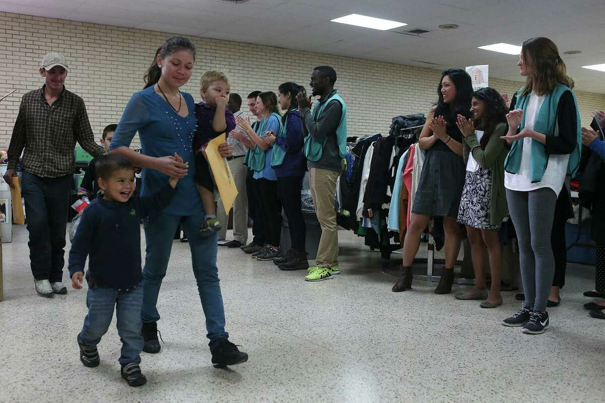 Sacred Heart Catholic Church immigrant shelter visitors and volunteers applaud as mostly Central American families arrive in McAllen, Texas, Tuesday, Jan. 19, 2016. The shelter serves as the first stop for immigrants released by immigration officials. It provided food, clothing and a place to clean up and rest.