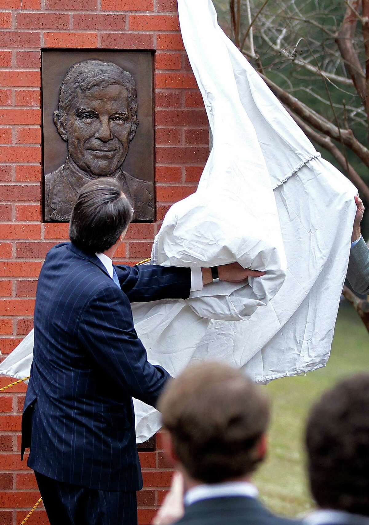 Robert Mosbacher, Jr. pulls a sheet off of one of the plaques during an invitation-only ceremony officially renaming the Preston Street Bridge near downtown in late Robert A. Mosbacher, Sr.'s honor on Wednesday, Jan. 20, 2016, in Houston. The event was attended by Former President and Mrs George H. W. Bush and former Secretary of State and Mrs. James A. Baker, III will join the family, friends and former colleagues of the late Robert A. Mosbacher, Sr.