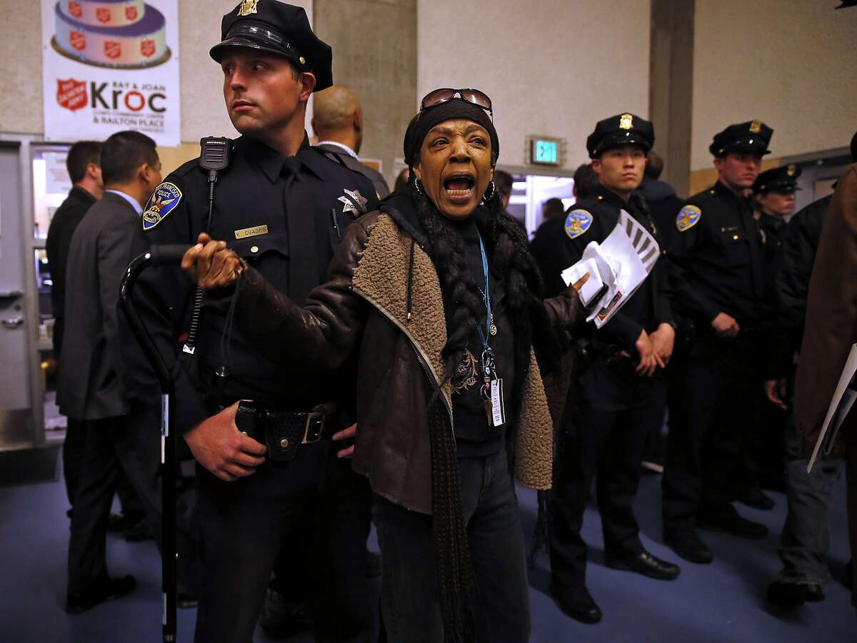 """A woman identifying herself as """"Grandma Tax Payer"""" yells as San Francisco Police officers exit during middle of Police Commission meeting at Salvation Army Kroc Center in San Francisco, Calif., on Wednesday, January 20, 2016."""