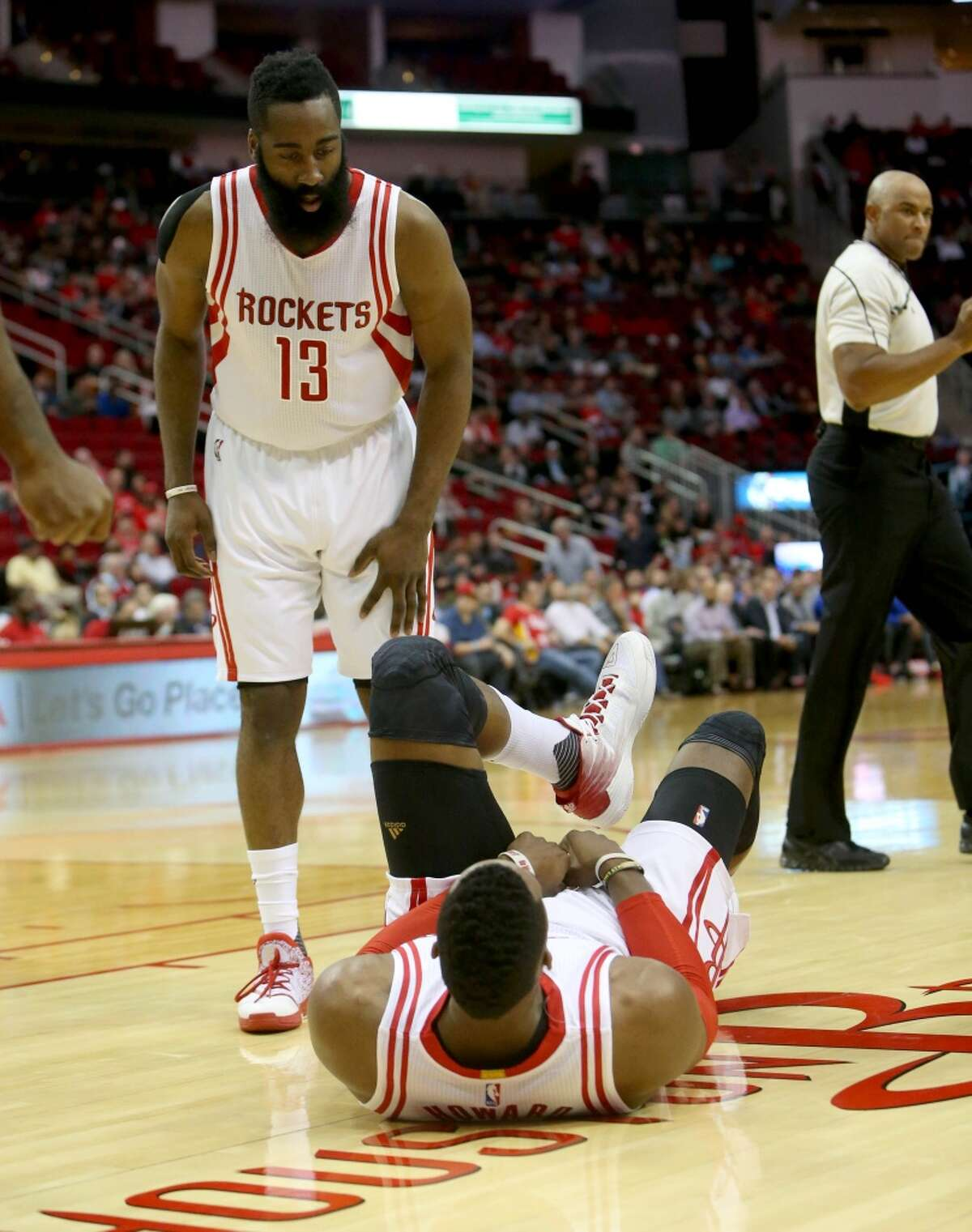 Houston Rockets guard James Harden (13) looks over Houston Rockets center Dwight Howard (12) lying on the floor after running into teammate Houston Rockets guard Ty Lawson (3) and Detroit Pistons forward Stanley Johnson (3) during the first quarter at the Toyota Center Wednesday, Jan. 20, 2016, in Houston. Howard left the game and went back into the locker room. ( Gary Coronado / Houston Chronicle )