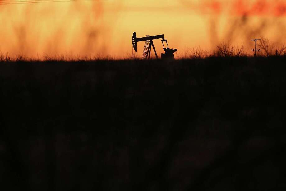 A pump jack works at dawn Wednesday in the Permian Basin. West Texas Intermediate crude futures slid to $26.55, hitting their lowest point in 13 years. Photo: Spencer Platt, Staff / 2016 Getty Images
