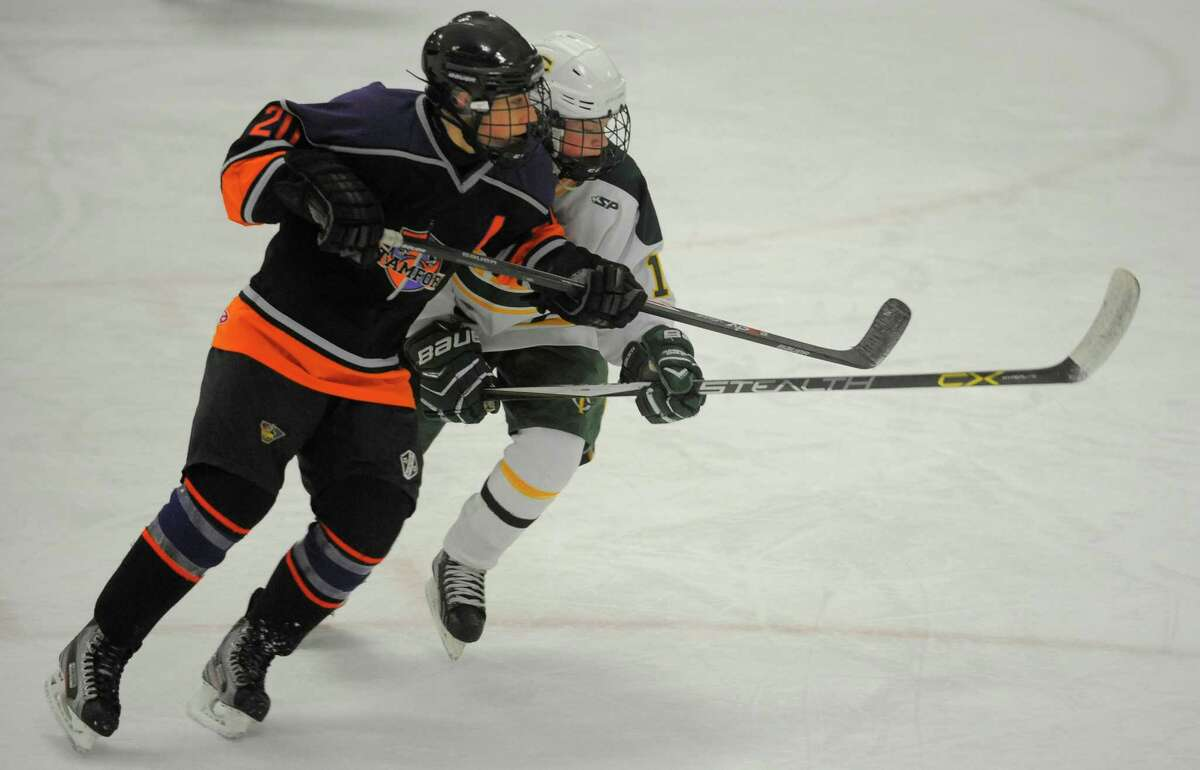 Westhill-Stamford's Nick Rich and Trinity Catholic's Logan Healy battle for position in the first period on Wednesday night at Terry Conners Rink.