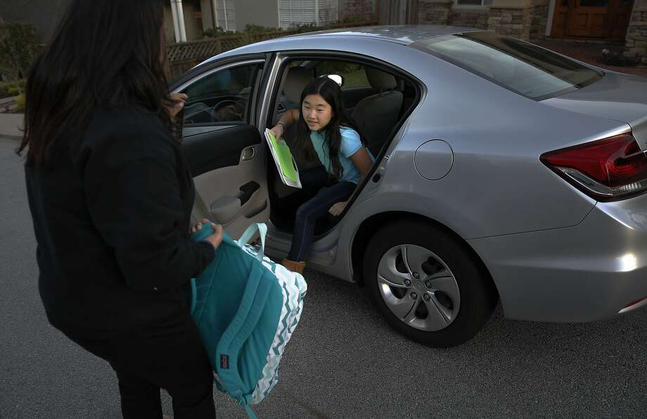 Zum driver Marcia Bravo drops off seventh grade student Ellie at her San Mateo home after being picked up from school in Portola Valley, Calif., on Wed. January 20, 2016.  Zum, which has childcare providers giving rides to kids are also be available to watch them in their homes. Photo: Michael Macor, The Chronicle
