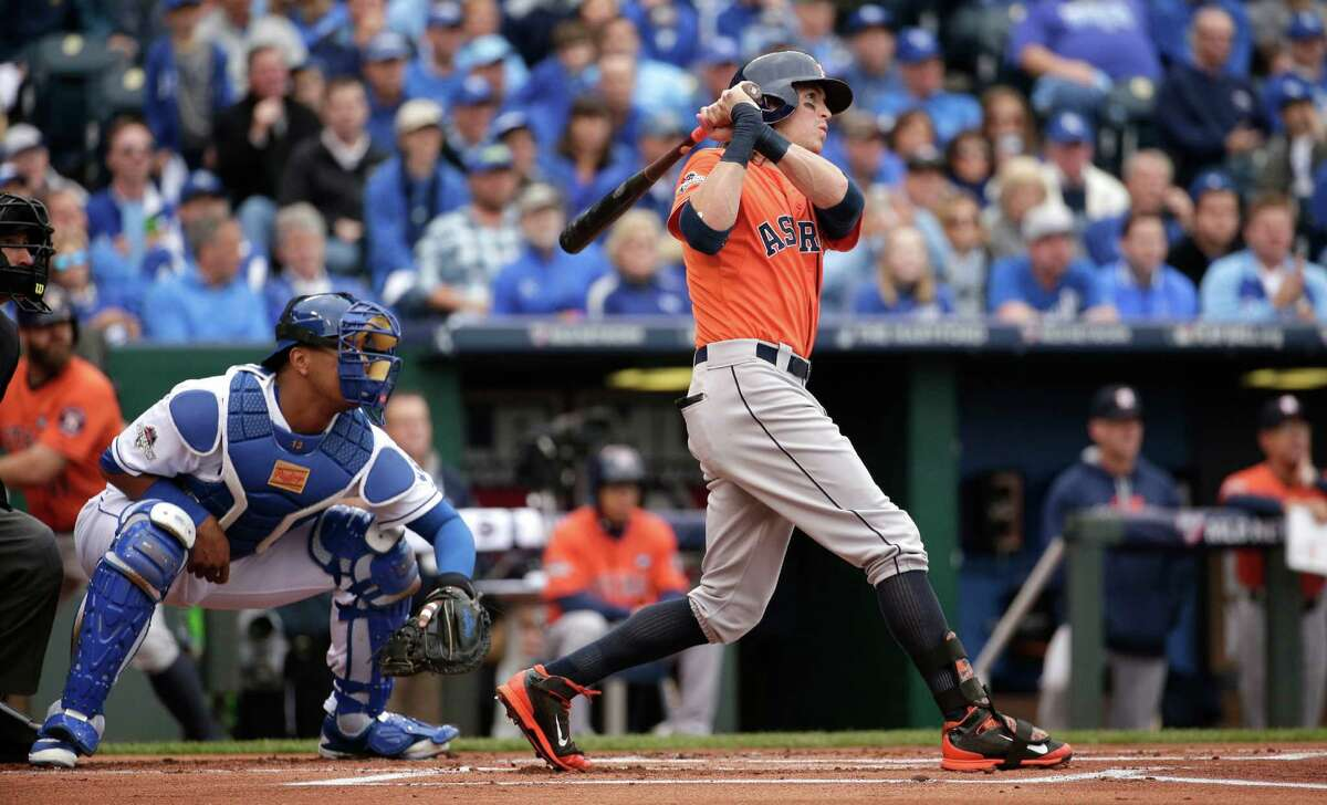 Houston Astros' Colby Rasmus, right, hits an RBI-double during the first inning of Game 2 in baseball's American League Division Series against the Kansas City Royals, Friday, Oct. 9, 2015, in Kansas City, Mo. (AP Photo/Charlie Riedel)