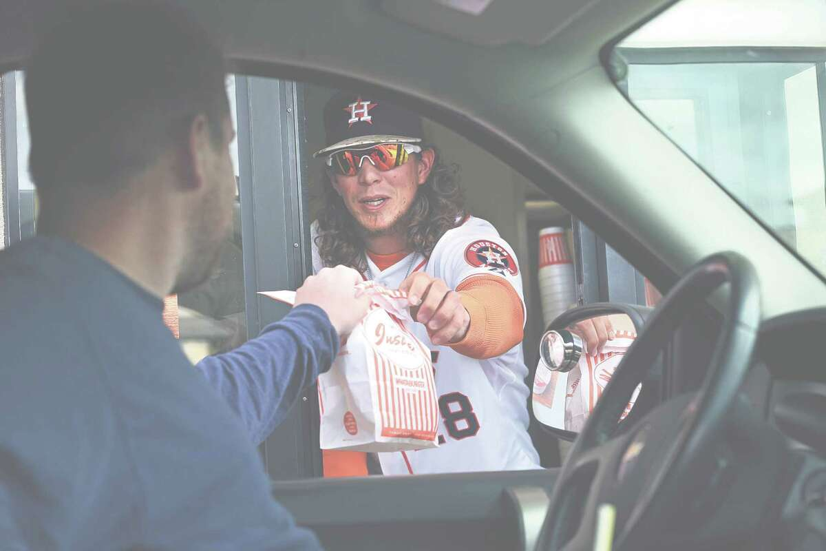 As part of one of Tuesday's stops tied to the Astros' annual winter caravan, outfielder Colby Rasmus works the drive-thru window at a San Antonio Whataburger.