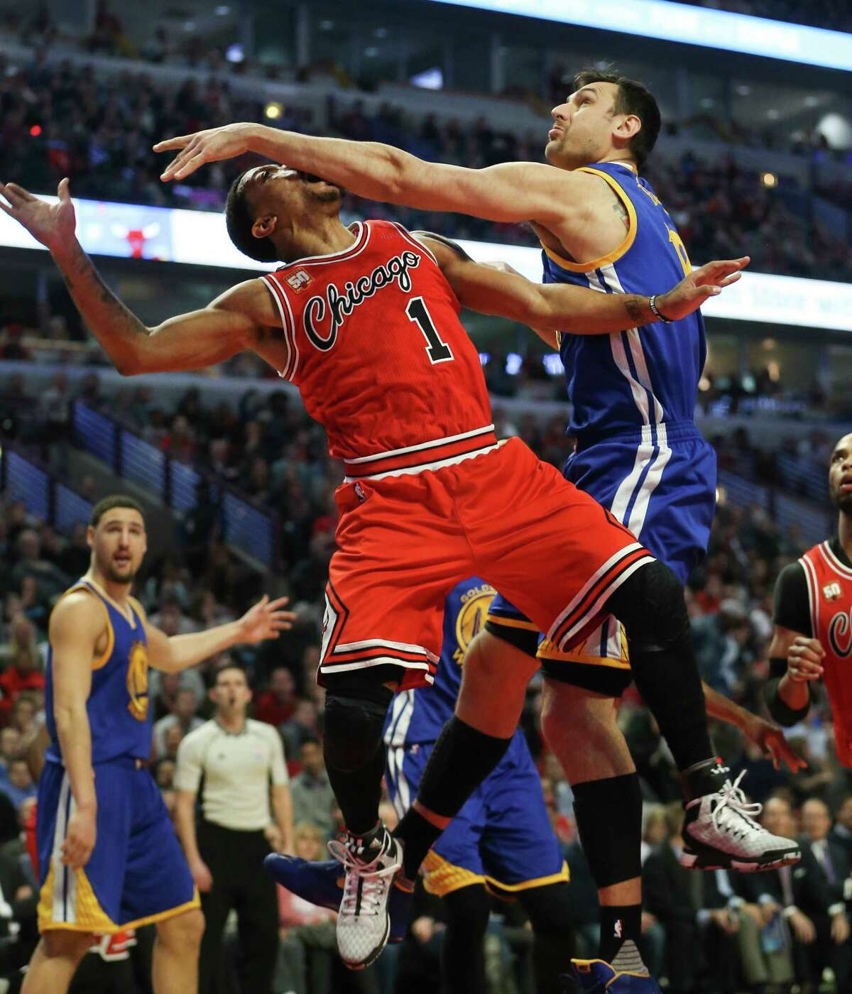 The Warriors' Andrew Bogut fouls the Bulls' Derrick Rose but fails to prevent Rose from making the shot.